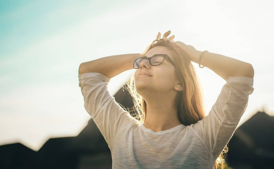 blonde woman wearing glasses looking upwards at golden hour