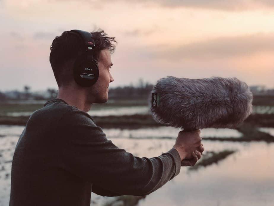 millennial man recording sound outdoors magic hour